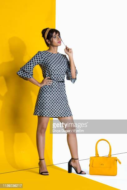 full length of woman standing against colored background - fashion stock pictures, royalty-free photos & images