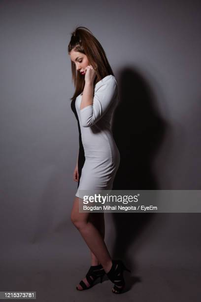 full length of woman standing against wall - bogdan negoita stock pictures, royalty-free photos & images
