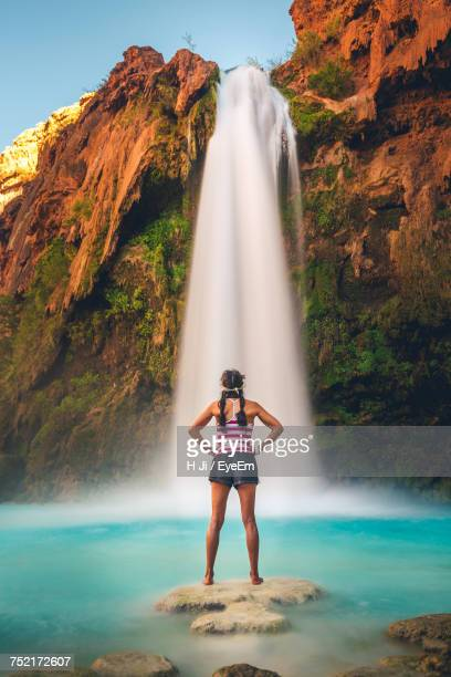 full length of woman standing against waterfall - grand canyon village stock photos and pictures