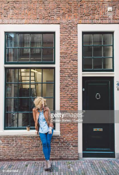 full length of woman standing against window - bortes stock pictures, royalty-free photos & images