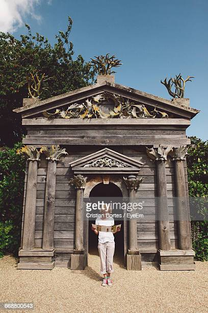 full length of woman standing against wooden historic building - bortes stockfoto's en -beelden