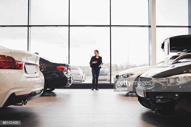 Full length of woman standing amidst cars in showroom