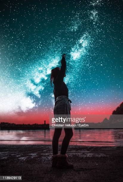 full length of woman standing at beach against starry sky - astronomy stock pictures, royalty-free photos & images