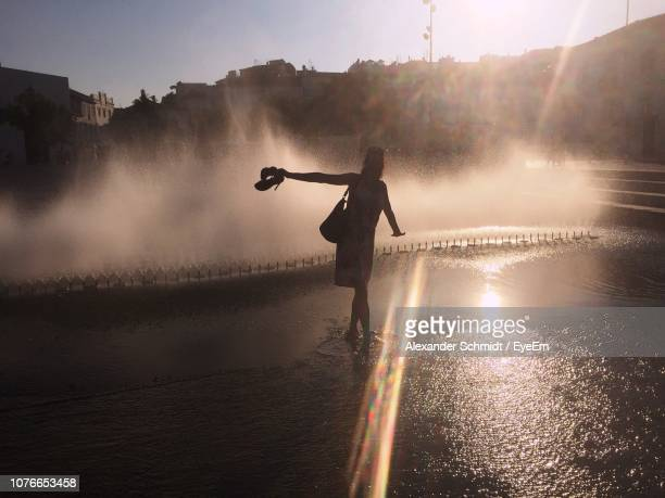 full length of woman standing by fountain - femme fontaine photos et images de collection
