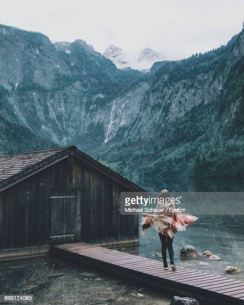 Full Length Of Woman Standing By Lake Cabin