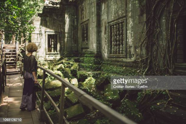 full length of woman standing by old building - bortes stockfoto's en -beelden