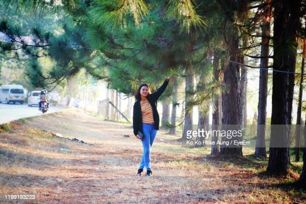 full length of woman standing by trees - ko ko htike aung stock pictures, royalty-free photos & images
