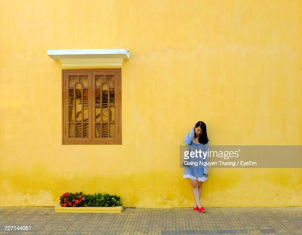 Full Length Of Woman Standing By Wall