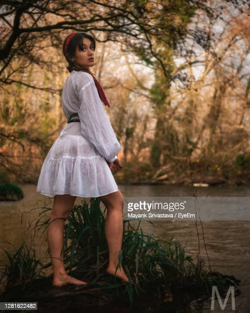 full length of woman standing by water - mini dress stock pictures, royalty-free photos & images