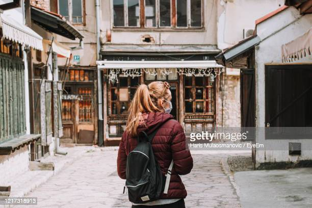 full length of woman standing empty street due to coronavirus - coronavirus winter stock pictures, royalty-free photos & images