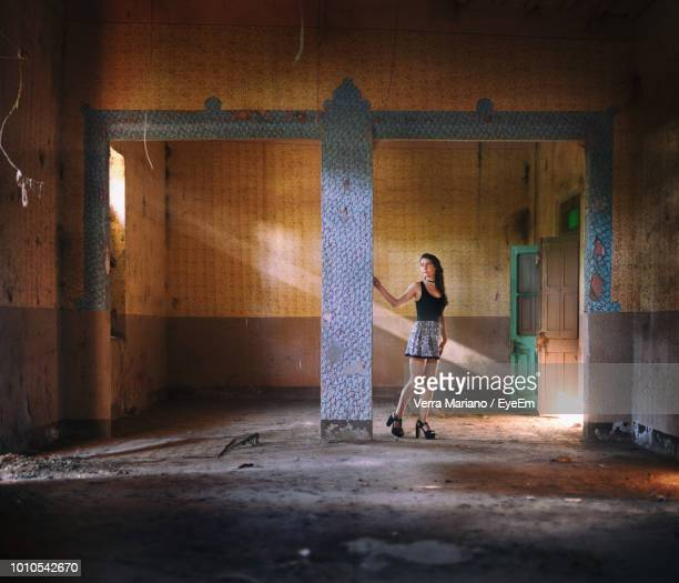 Full Length Of Woman Standing In Abandoned House