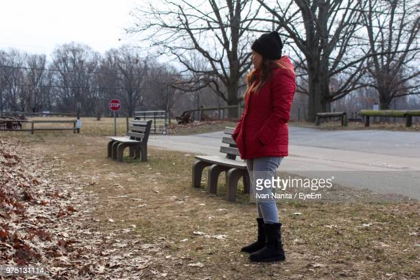 Full Length Of Woman Standing In Park Against Bare Trees During Winter