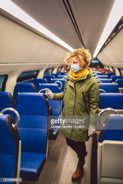 full length of woman standing in train - bortes stock pictures, royalty-free photos & images