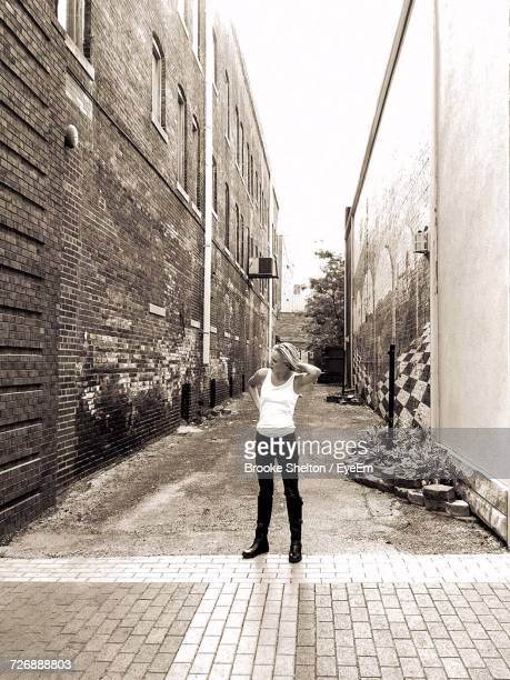 Full Length Of Woman Standing On Alley Amidst Buildings