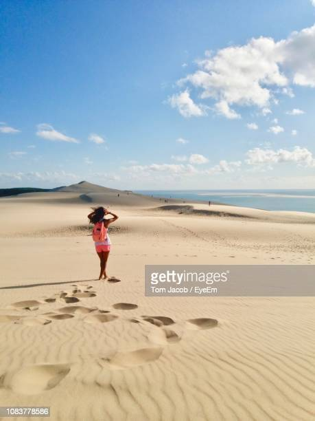 full length of woman standing on beach against sky - gironde stock pictures, royalty-free photos & images