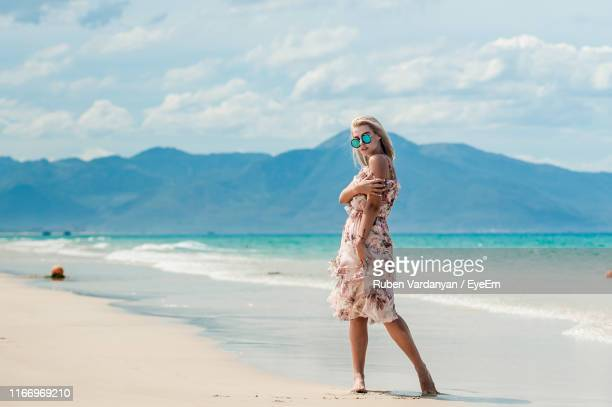 full length of woman standing on beach against sky - ruben vardanyan stock pictures, royalty-free photos & images