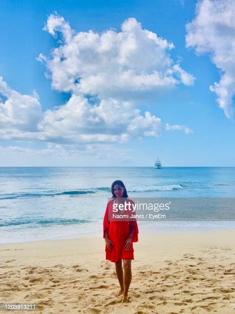 full length of woman standing on beach against sky - naomi jarvis stock pictures, royalty-free photos & images