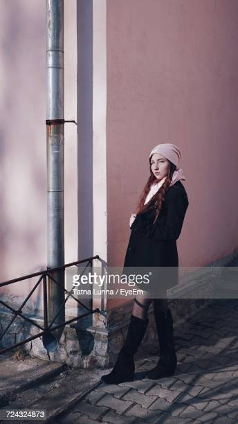 Full Length Of Woman Standing On Cobbled Street By Pink Wall