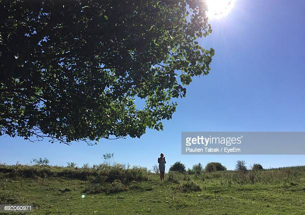 full length of woman standing on field against clear blue sky during sunny day - paulien tabak stock-fotos und bilder