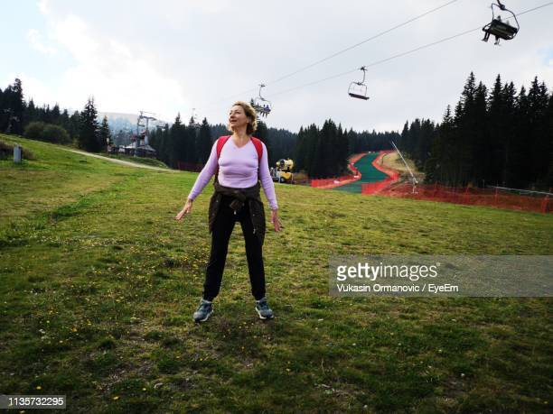full length of woman standing on field - ski lift stock pictures, royalty-free photos & images