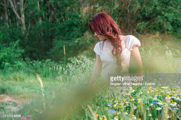 full length of woman standing on field - bogdan negoita stock pictures, royalty-free photos & images