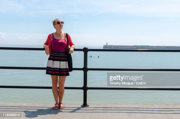 full length of woman standing on pier over sea against sky - folkestone stock pictures, royalty-free photos & images