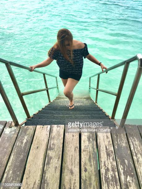 full length of woman standing on pier over sea - jessa stock pictures, royalty-free photos & images