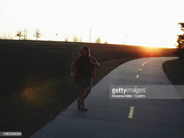 full length of woman standing on road against sky during sunset - rowena miller stock photos and pictures