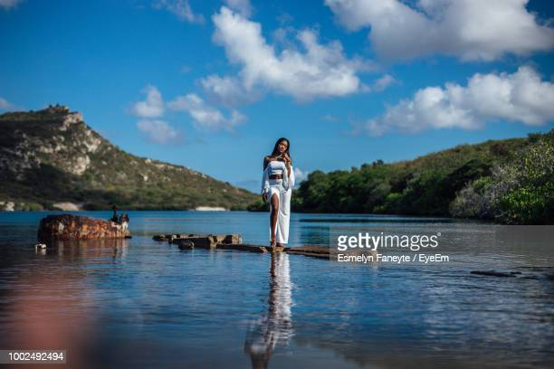 full length of woman standing on rock amidst lake against sky - ウォーターフロント ストックフォトと画像