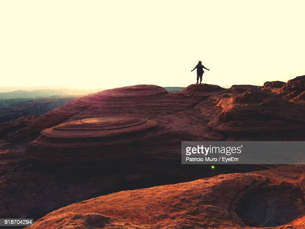 full length of woman standing on rock formation against sky - muro stock photos and pictures