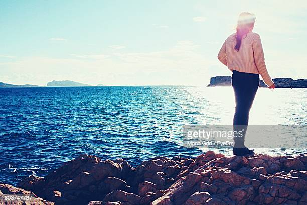 Full Length Of Woman Standing On Rocky Sea Shore Against Sky
