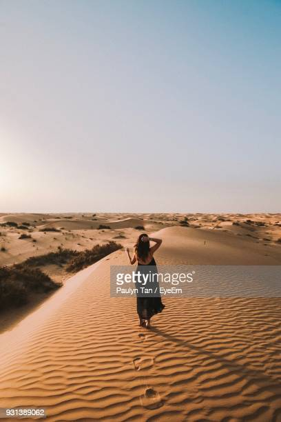 full length of woman standing on sand dune in desert against sky - dubai strand stock-fotos und bilder