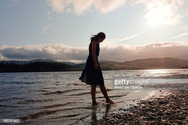 Full Length Of Woman Standing On Shore Against Cloudy Sky