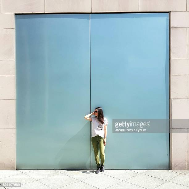 Full Length Of Woman Standing On Sidewalk Against Blue Gate