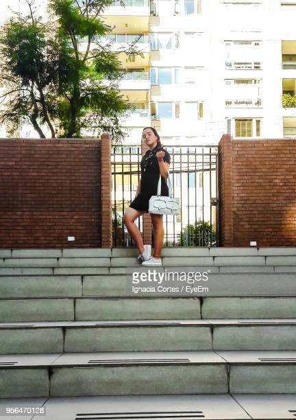 Full Length Of Woman Standing On Steps Against Building