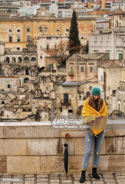 full length of woman standing on terrace against buildings in city - matera stock photos and pictures