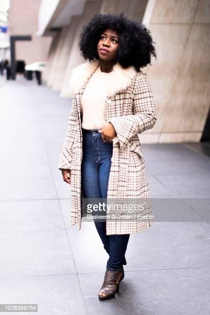 full length of woman standing outdoors - overcoat stock pictures, royalty-free photos & images