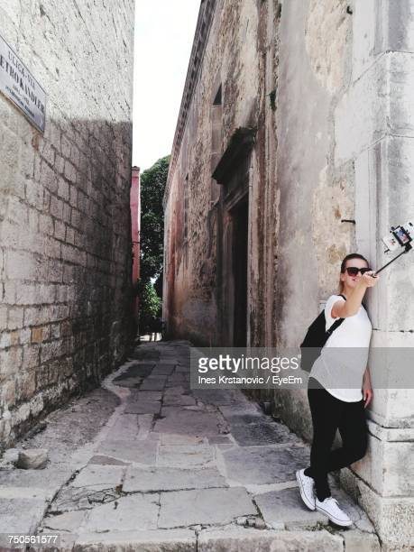 Full Length Of Woman Taking Selfie Through Phone While Standing By Old House In Alley