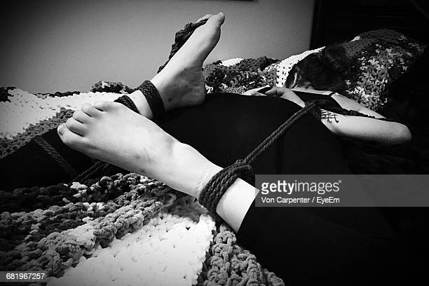 full length of woman tied with rope on bed at home - female torture stock-fotos und bilder