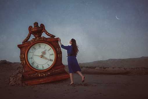 Full Length Of Woman Touching Clock On Sand At Beach Against Sky - gettyimageskorea