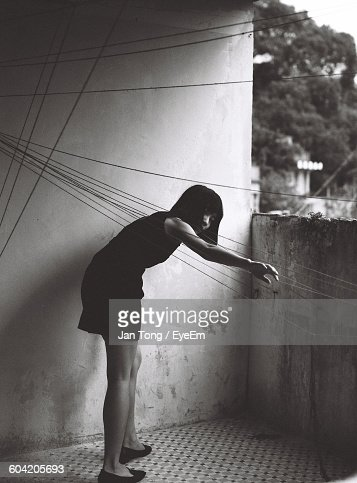 Full Length Of Woman Touching Wires Against Wall