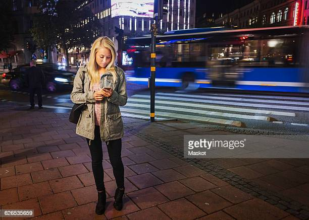 Full length of woman using mobile phone on sidewalk in city at night