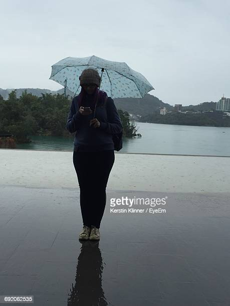 Full Length Of Woman Using Phone While Standing With Umbrella On Promenade In Rain