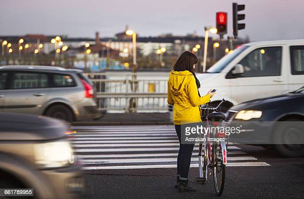 full length of woman using smart phone while standing with bicycle on city street - パーカー服 ストックフォトと画像
