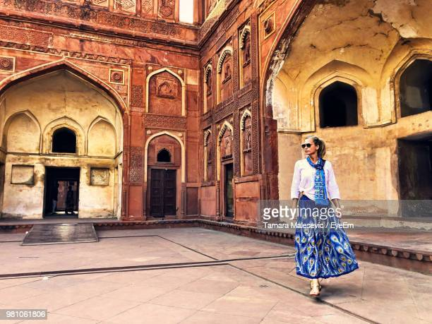 Full Length Of Woman Walking Against Historic Building