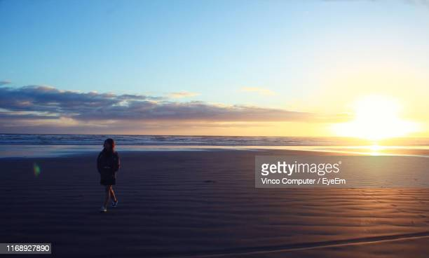 full length of woman walking at beach against sky during sunset - invercargill stock pictures, royalty-free photos & images
