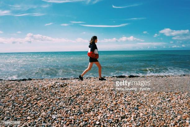full length of woman walking at beach against sky - folkestone stock pictures, royalty-free photos & images