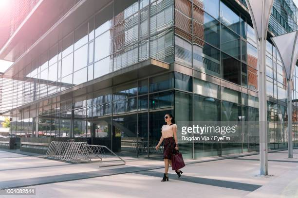 full length of woman walking by modern building in city - bankenviertel stock-fotos und bilder