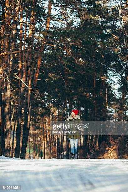 Full length of woman walking in snow covered forest