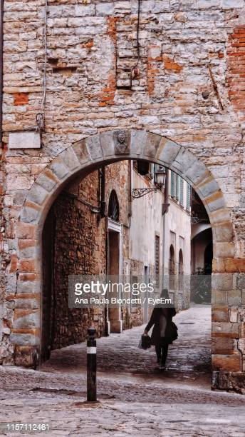 full length of woman walking on archway - bergamo stock pictures, royalty-free photos & images